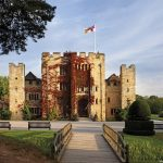 Hever Castle, a fortified house with flag flying, the entrance viewed from the gardens.